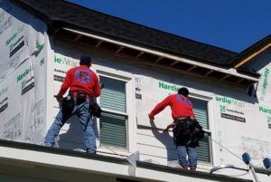Workers putting siding on house